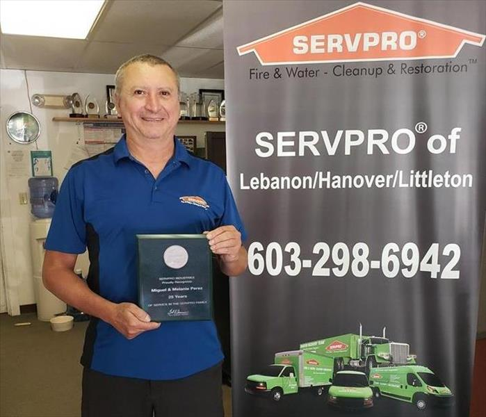 man standing next to a SERVPRO sign holding a 25th anniversary recognition plaque