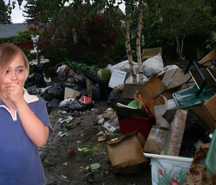 girl standing in yard filled with garbage and junk