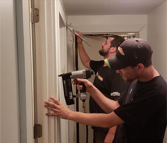 Two men putting up drywall