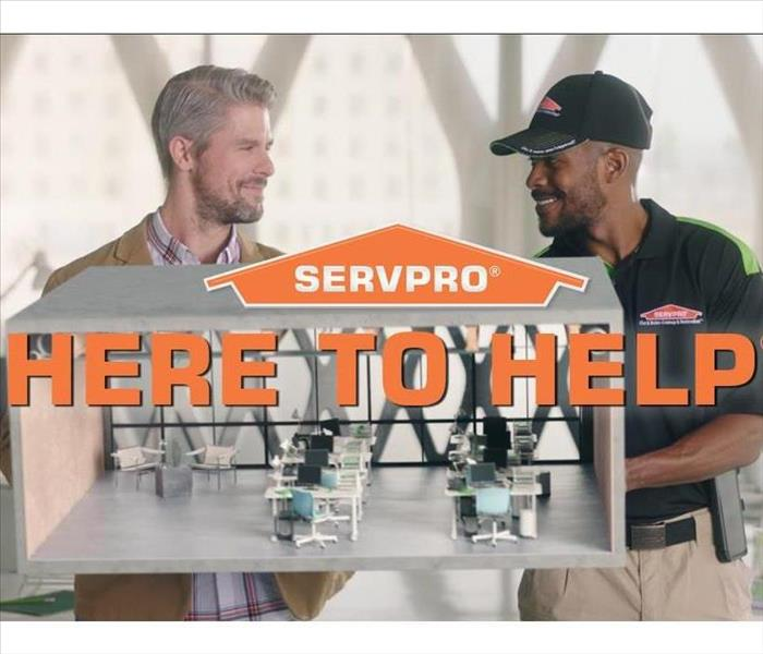 servpro employee and client standing behind servpro logo and here to help