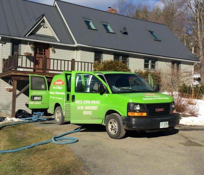 bright green servpro van parked in front of a home