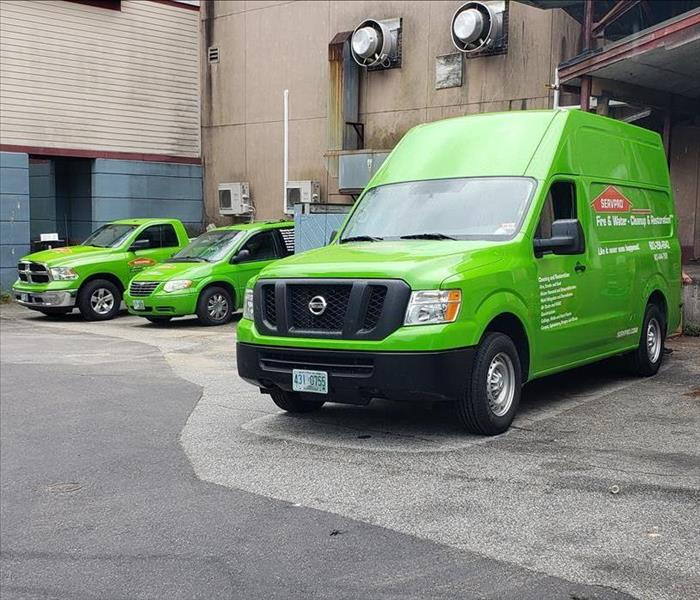 three bright green servpro work vehicles in front of business