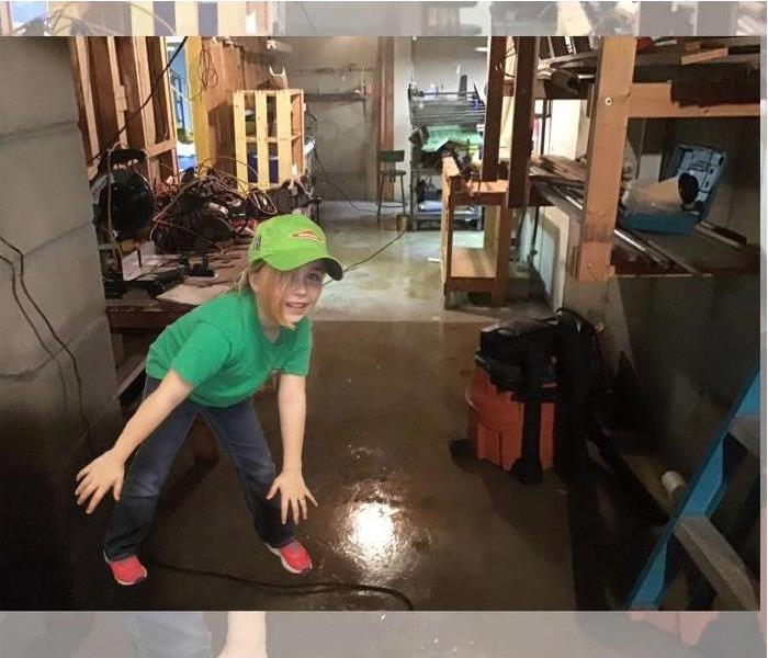 young girl standing in a basement full of shelves holding random things showing flooded basement floor